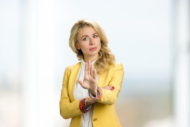Junge geschäftsfrau, die halt gestikuliert. junge blonde geschäftsdame zeigt stoppgeste.