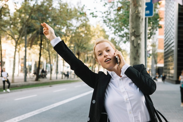 Junge geschäftsfrau, die hand für das stoppen des autos auf stadtstraße anhebt