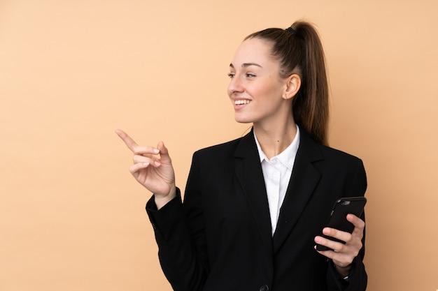 Junge geschäftsfrau, die handy über isolierte wand verwendet, die zur seite zeigt, um ein produkt zu präsentieren