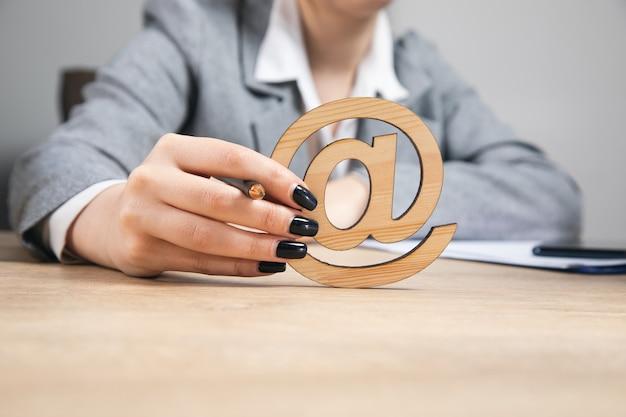 Junge geschäftsfrau, die hölzernes e-mail-zeichen hält