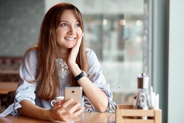 Junge geschäftsfrau, die ihr smartphone benutzt und im kaffeehaus lächelt