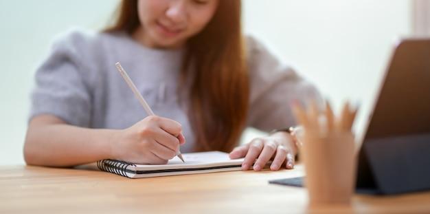 Junge geschäftsfrau, die ihre idee auf notizbuch schreibt