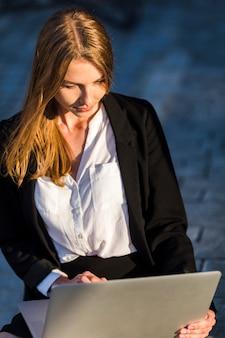 Junge geschäftsfrau, die ihren laptop betrachtet