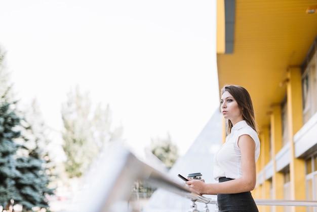 Junge geschäftsfrau, die im balkon hält mobiltelefon und wegwerfkaffeetasse steht