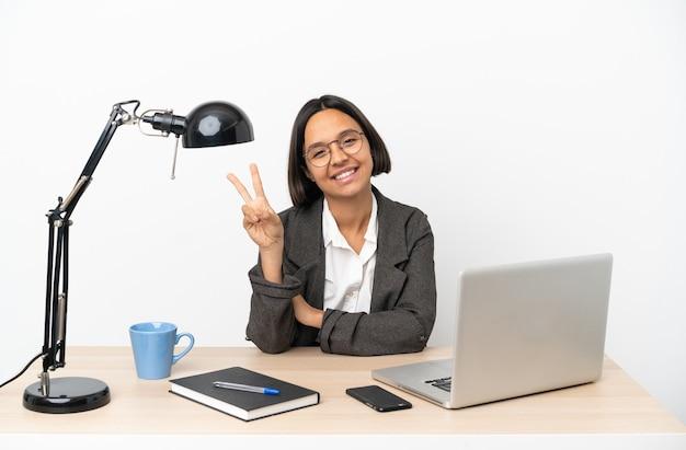 Junge geschäftsfrau, die im büro arbeitet, lächelt und zeigt siegeszeichen