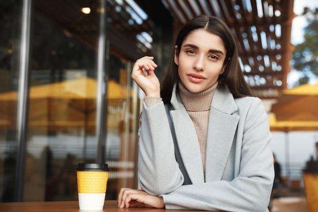 Junge geschäftsfrau, die im café draußen sitzt und die kamera selbstbewusst betrachtet.