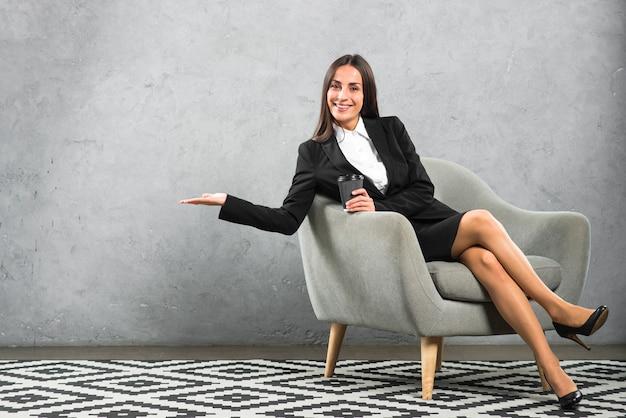 Junge geschäftsfrau, die im lehnsessel hält das wegwerfkaffeetassendarstellen sitzt