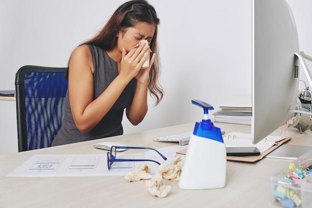 Junge geschäftsfrau, die im papiertaschentuch niest, wenn sie an ihrem schreibtisch-, grippe- und allergiekonzept sitzt