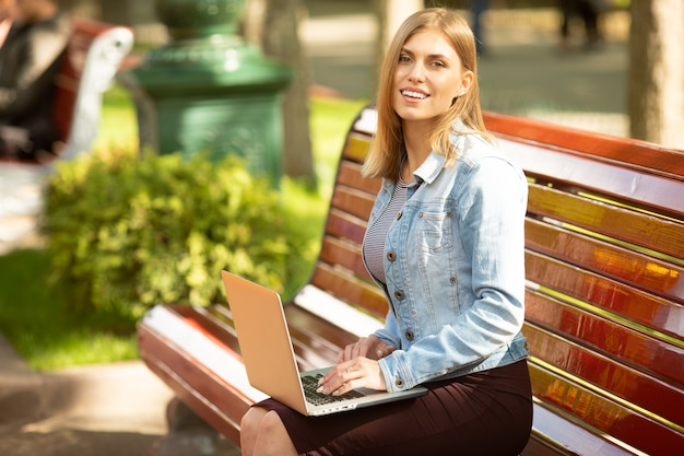 Junge geschäftsfrau, die im park sitzt und mit laptop arbeitet