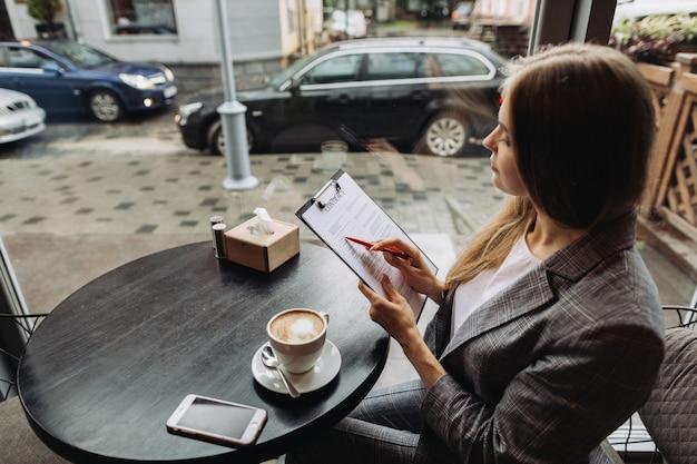 Junge geschäftsfrau, die in einem café arbeitet