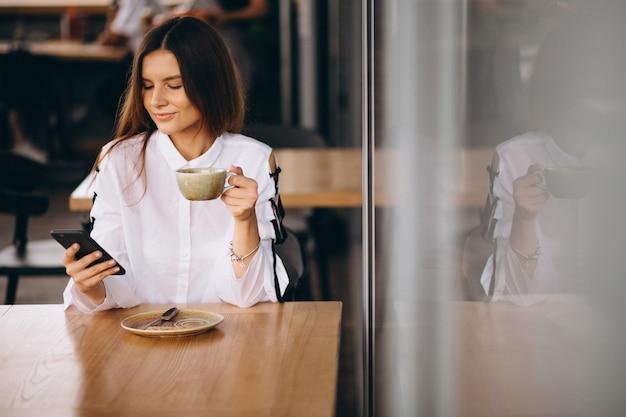 Junge geschäftsfrau, die in einem café mit kaffee und telefon sitzt