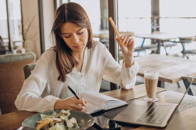 Junge geschäftsfrau, die in einem café zu mittag isst und am computer arbeitet