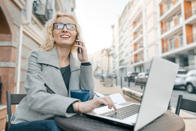 Junge geschäftsfrau, die in einem straßencafé mit laptop sitzt