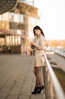 Junge geschäftsfrau, die in einer großstadt steht, sieht aus