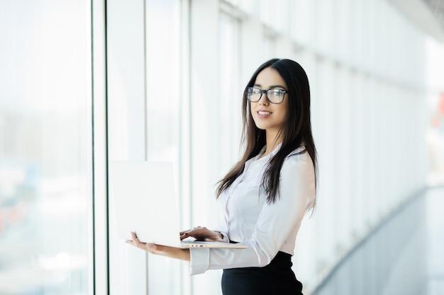 Junge geschäftsfrau, die in ihrem luxusbüro arbeitet, das einen laptop hält, der gegen panoramafenster mit blick auf geschäftsviertel steht