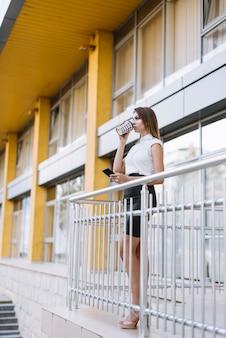 Junge geschäftsfrau, die in trinkendem kaffee des balkons in der hand smartphone halten steht