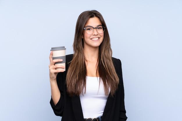 Junge geschäftsfrau, die kaffee hält, um wegzunehmen