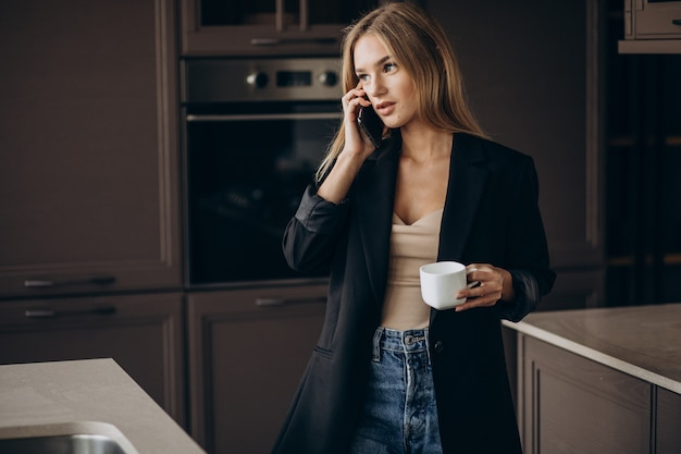 Junge geschäftsfrau, die kaffee trinkt und am telefon an der küche spricht