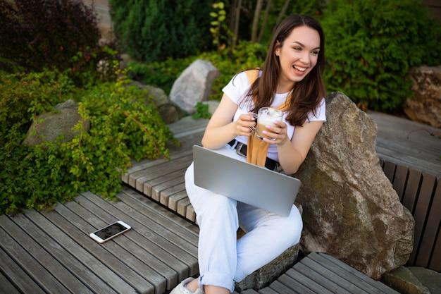 Junge geschäftsfrau, die kaffee trinkt und freiberuflich auf der straße arbeitet.