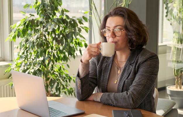 Junge geschäftsfrau, die kaffeepause bei der arbeit auf laptop-computer im büro hat