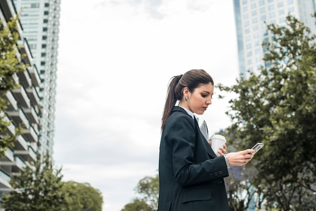 Junge geschäftsfrau, die kaffeetasse unter verwendung des handys an draußen hält