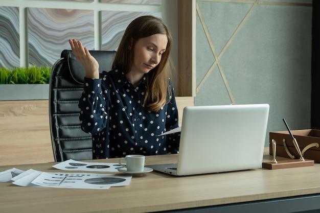 Junge geschäftsfrau, die kopfschmerzen hat, während sie im büro sitzt und sich müde und gestresst über ihre arbeitsprobleme fühlt