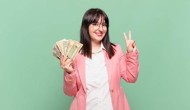 Junge geschäftsfrau, die lächelt und freundlich aussieht, die nummer zwei oder die zweite mit der hand nach vorne zeigt, herunterzählt