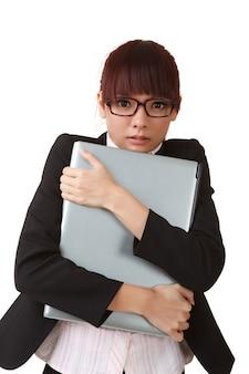 Junge geschäftsfrau, die laptop, nahaufnahmeporträt auf weißem hintergrund hält.