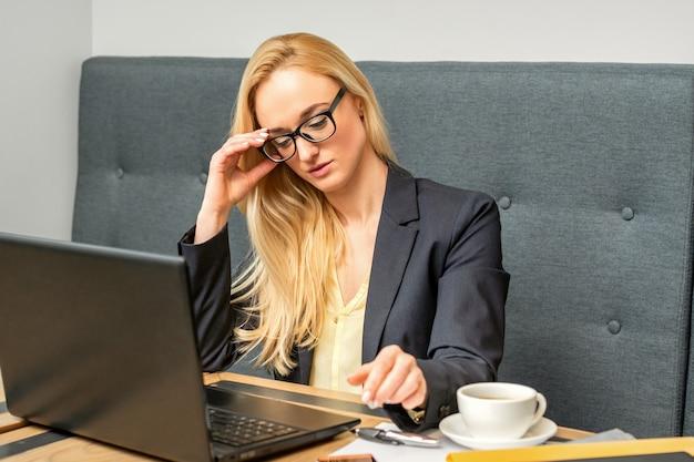 Junge geschäftsfrau, die laptop verwendet, der am tisch in einem café sitzt