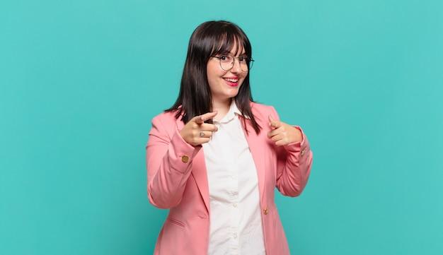 Junge geschäftsfrau, die mit einer positiven, erfolgreichen, glücklichen haltung lächelt, die auf die kamera zeigt und waffenzeichen mit den händen macht