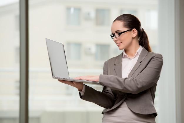 Junge geschäftsfrau, die mit laptop im geschäftskonzept arbeitet