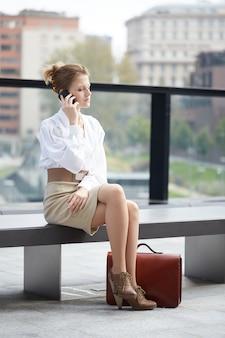 Junge geschäftsfrau, die mit mobile in der städtischen umwelt spricht