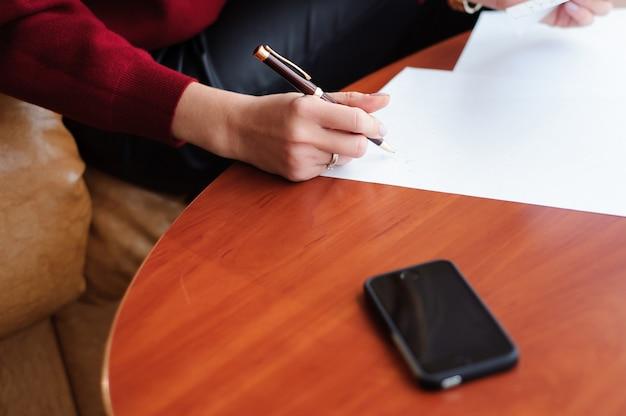 Junge geschäftsfrau, die mit papieren in einer lounge arbeitet.