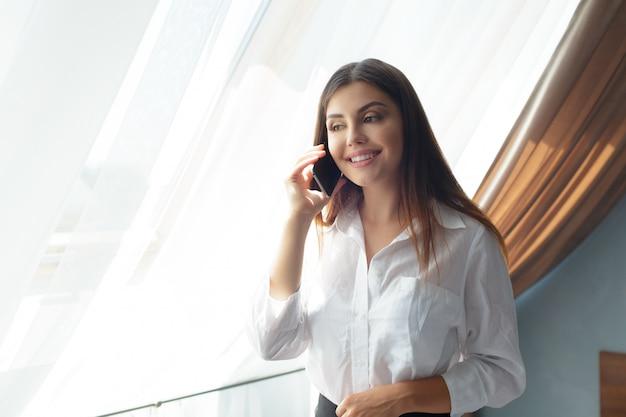 Junge geschäftsfrau, die mit telefon im hotel spricht.