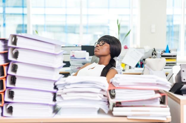Junge geschäftsfrau, die mit vielen arbeiten im büro schläft