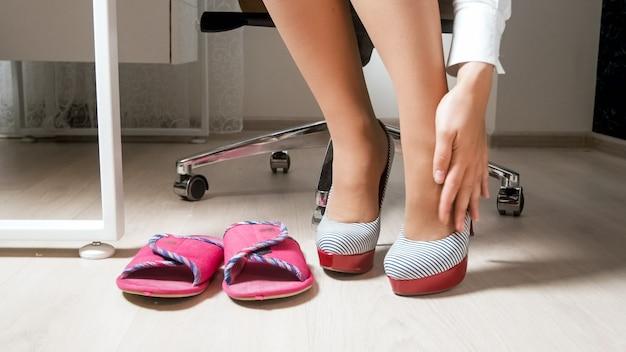 Junge geschäftsfrau, die nach dem tragen von schuhen mit hohen absätzen schmerzen und krampfadern in den beinen verspürt.