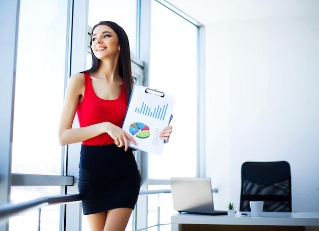 Junge geschäftsfrau, die nahe dem großen fenster im büro steht.