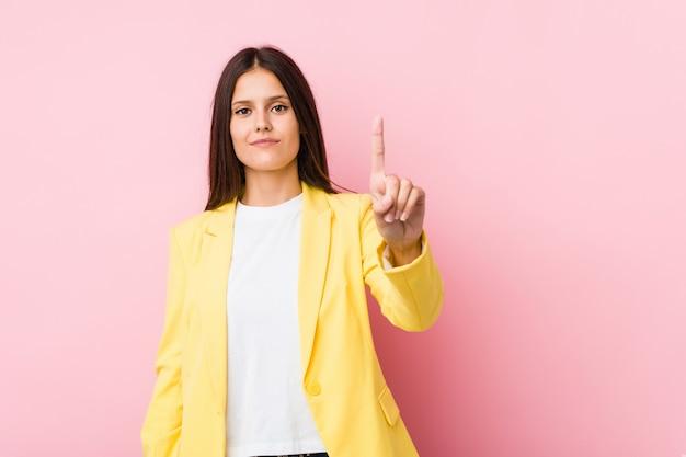 Junge geschäftsfrau, die nummer eins mit dem finger zeigt.