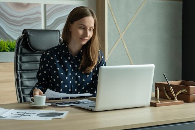 Junge geschäftsfrau, die online arbeitet und e-mails auf dem laptop überprüft, um den arbeitsprozess im büro zu organisieren?