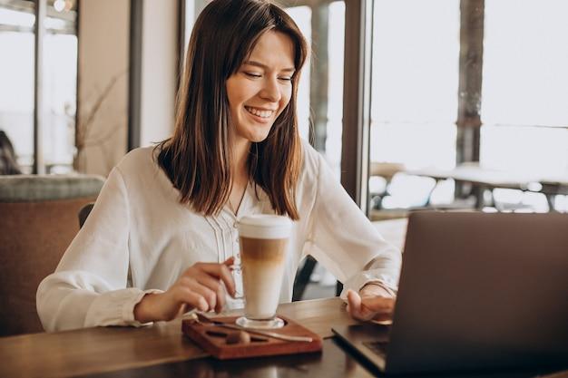 Junge geschäftsfrau, die online in einem café arbeitet und kaffee trinkt