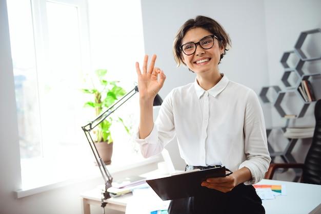 Junge geschäftsfrau, die ordner hält, lächelt, gruß am arbeitsplatz im büro.