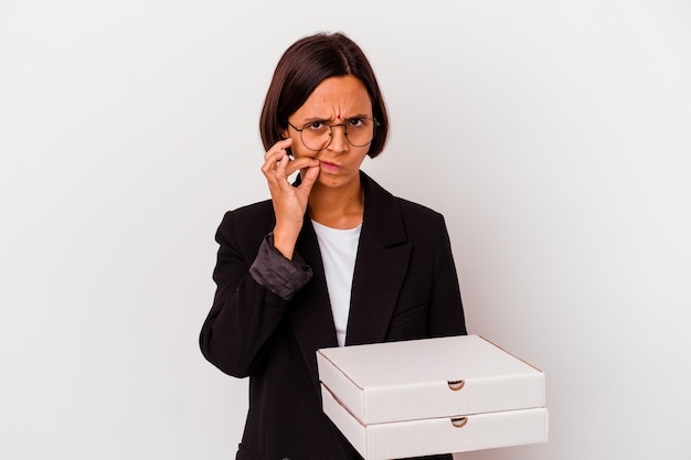 Junge geschäftsfrau, die pizzen hält, isoliert mit den fingern auf den lippen, die ein geheimnis halten.