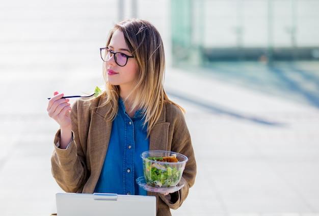 Junge geschäftsfrau, die salat isst und mit computer an städtischem im freien arbeitet