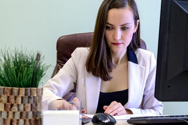 Junge geschäftsfrau, die schwer über dem schreibtisch in der studie, wirtschaftsprüferfinanzberichterstattung arbeitet