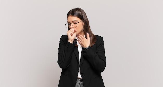 Junge geschäftsfrau, die sich mit halsschmerzen und grippesymptomen krank fühlt und mit bedecktem mund hustet