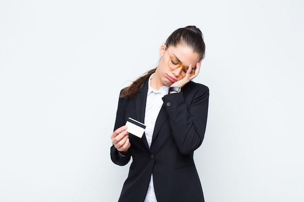 Junge geschäftsfrau, die sich nach einer lästigen, langweiligen und mühsamen aufgabe gelangweilt, frustriert und schläfrig fühlt und gesicht mit hand mit banknoten mit rechnungen hält