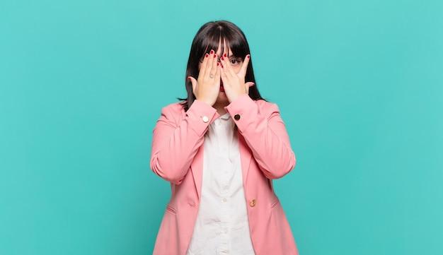 Junge geschäftsfrau, die sich verängstigt oder verlegen fühlt, mit halb mit händen bedeckten augen späht oder ausspioniert