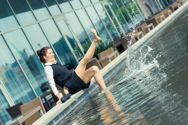 Junge geschäftsfrau, die spaß nahe bei swimmingpool hat