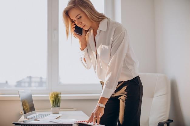 Junge geschäftsfrau, die telefon im büro benutzt