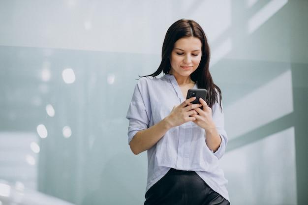 Junge geschäftsfrau, die telefon im büro verwendet